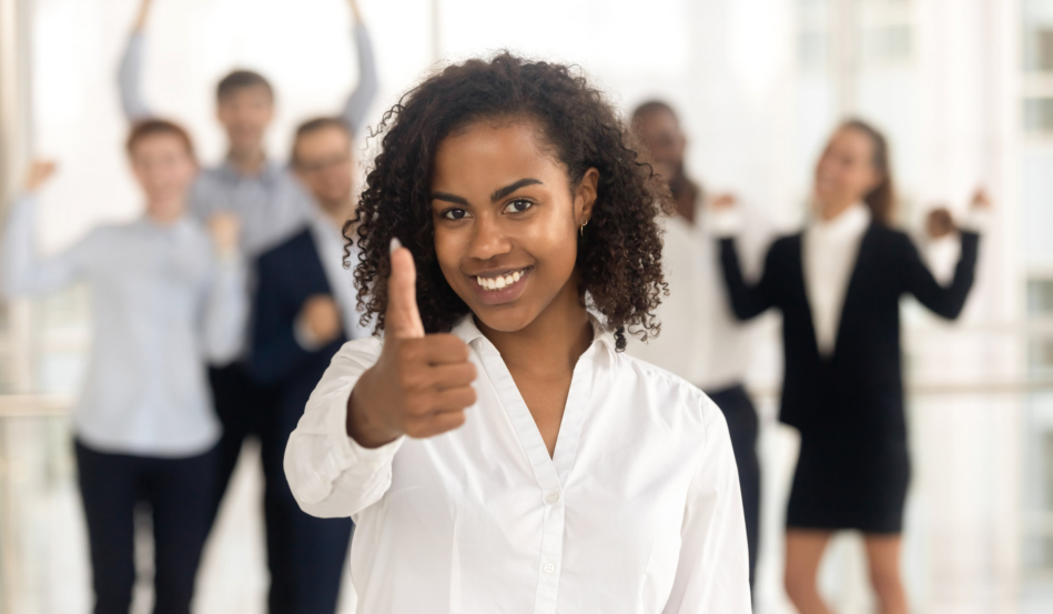 Satisfied african female showing thumbs up happy employees in background