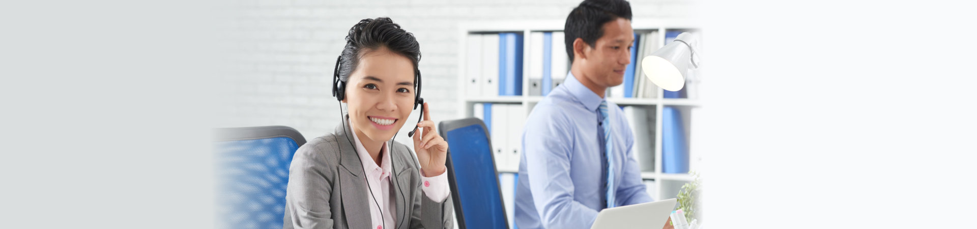 cheerful business woman in headset and man working in office